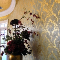 Polished raised venetian plaster patterns over textured gold leaf